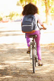 Rear View Of Young Woman Cycling Along Street To Work Stock Photo