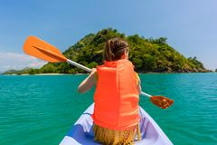Rear view of young woman experiencing freedom during vacation. Rear view of young woman experiencing freedom while paddling in a sunny day of summer during Royalty Free Stock Photo