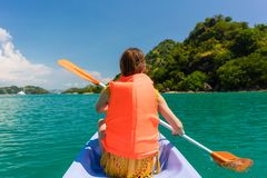Rear view of young woman experiencing freedom during vacation in. Rear view of young woman experiencing freedom while paddling in a sunny day of summer during Stock Photography