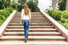 Rear view of young woman going up stairs in park Royalty Free Stock Photos