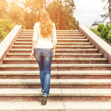 Rear view of young woman going up stairs in park. Rear view of young woman going up the stairs in the park Royalty Free Stock Photography