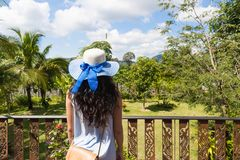 Rear View Of Young Woman In Hat And Dress On Balcony Or Terrace Enjoy Tropical Forest Landscape Royalty Free Stock Photo