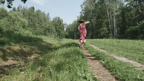 Rear view of young woman in hat running along the path, slow motion