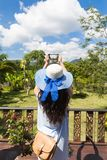 Rear View Of Young Woman In Hat Taking Photo Of Tropical Forest On Smart Phone From Balcony Stock Photos