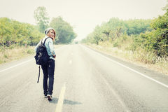 Rear view of a young woman hitchhiking carrying backpack walking Royalty Free Stock Photography