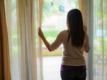 Sad Woman looking out a window, indoors. Rear view of a young woman holding the curtains open to look out of a large light window at home, interior. Positive Stock Images