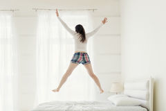 Rear view of young woman jumping up on bed at home Stock Photos