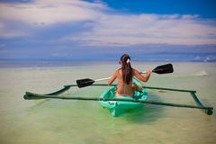Rear view of a young woman kayaking in the clear Royalty Free Stock Photos