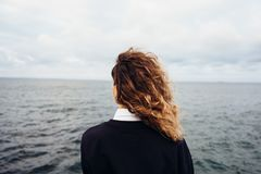 Rear view of young woman looking at overcast sky and gray sea. Female with red curly hair standing alone thinking at the background of seascape royalty free stock image