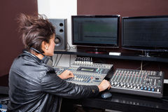 Rear View Of Young Woman Mixing Audio. In recording studio royalty free stock photography