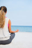 Rear view of young woman practicing yoga at beach Stock Images