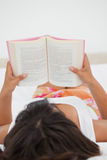 Rear view of a young woman reading a novel Royalty Free Stock Photos