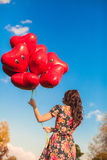 Rear view of young woman with red balloons in hand background blue sly Stock Images