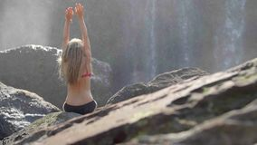 Woman By Waterfall. Rear view of young woman sitting in front of waterfall with her hands raised. Female tourist with her arms outstretched. Freedom, success stock video
