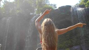 Woman By Waterfall. Rear view of young woman sitting in front of waterfall with her hands raised. Female tourist with her arms outstretched. Freedom, success stock video footage