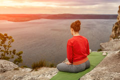 Rear view of young woman sitting in lotus position on the rock over the river. Rear view of young woman sitting in lotus position on the rock over the big river Stock Image
