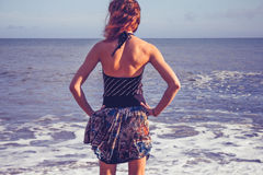 Rear view of young woman standing on beach looking at sea Royalty Free Stock Photography