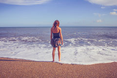 Rear view of young woman standing on beach looking at sea Stock Images