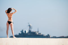 Rear view of young woman standing on open air. Brunette in black swimwear observing military ship. Rear view of young woman standing on open air Stock Image