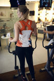 Rear view of young woman. Using aerobic exercise machine in gym Stock Image