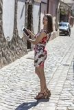Young Woman Using a Tablet. Rear view of a young woman is using a tablet and looking back over the shoulder in an old paved city street Royalty Free Stock Photo