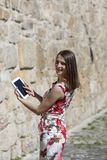 Young Woman Using a Tablet. Rear view of a young woman is using a tablet and looking back over the shoulder in an old paved city street Royalty Free Stock Image