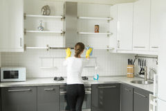 Rear view at a young woman washing kitchen closet Royalty Free Stock Images