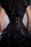 Rear view of young woman wearing elegant black corset Stock Photos