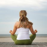 Rear view young woman in yoga pose at the beach. Rear view portrait of a young woman in yoga pose at the beach Royalty Free Stock Photography