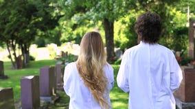 Women talking at cemetery near tombstone