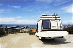 Rear of vintage camper parked on the beach seaside with a surfboard on back - Leisure trip in the summer.  royalty free stock photography