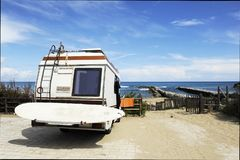 Rear of vintage camper parked on the beach seaside with a surfboard on back - Leisure trip in the summer.  royalty free stock images