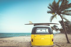 Rear of vintage car parked on the tropical beach seaside with a surfboard on the roof. Leisure trip in the summer. retro color effect stock image