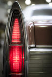Rear vintage tail light. Tall thin pointed rear vintage tail light in the wing of an oldtimer classic motor car illuminated to show the red coloring, close up Stock Photography