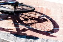 Rear wheel of a bicycle and its shadow on paving stones Stock Photo
