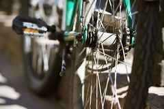 The rear wheel and part of a modern turquoise bike. Standing on the street and stained with dirt, as well as illuminated by sunlight stock image