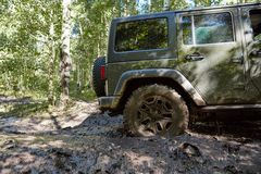 Rear wheel of a 4WD bogged down in soft mud. On a forest track in a close up side view during an off-road expedition Royalty Free Stock Photo