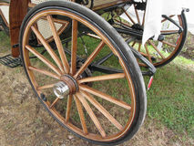 Rear wheels of old-fashioned horse carriage on green grass Stock Photography