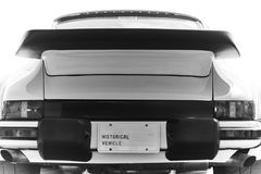 Rear of wide body of retired antique German racing car with black spoiler. Black & white photo of a white iconic historical vehicle as seen from the rear of the royalty free stock image