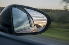 Rear window of auto with view of sundown landscape.  Royalty Free Stock Image