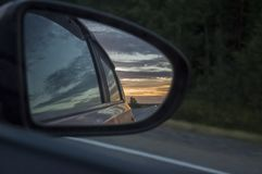 Rear window of auto with view of sundown landscape.  Stock Photos