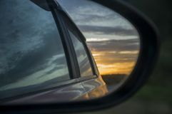 Rear window of auto with view of sundown landscape.  Stock Photo