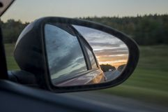 Rear window of auto with view of sundown landscape.  Stock Photography