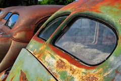 Rear windows of a collection of old rusty cars stock images