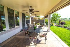 Modern Home Rear Yard Patio. Rear Yard Covered Patio With Furniture And Sun Screens On Modern Home Royalty Free Stock Photos