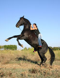 Rearing black horse. Beautiful young woman and her friend rearing Stock Image