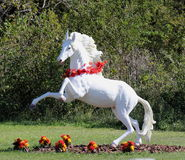 Rearing White Horse Garden Figure. Life size rearing white horse in garden setting Stock Photo