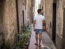 Rearview человека идя в старый итальянский городок стоковое фото rf
