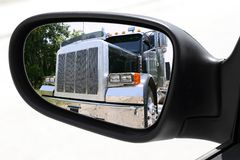 Rearview car driving mirror overtaking big truck Royalty Free Stock Photography