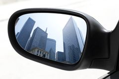 Rearview car driving mirror view city downtown Royalty Free Stock Photos